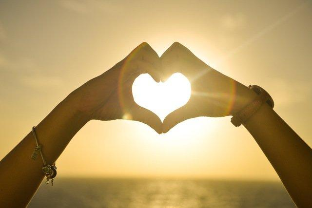 Woman making heart shape with hands at sunset